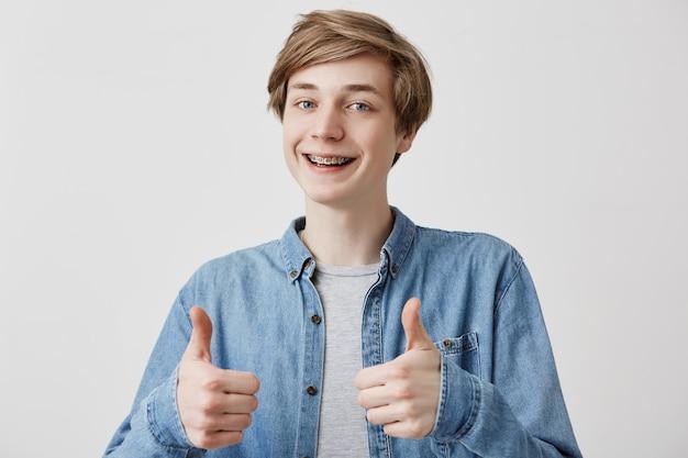 Portret van gelukkige jonge man met eerlijke haren geven twee duimen omhoog gebaar in volle tevredenheid geïsoleerd tegen een grijze achtergrond. positieve menselijke emotie, gezichtsuitdrukking, lichaamstaal