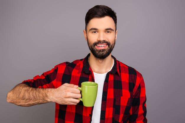 Portret van gelukkige jonge man met groene kopje thee
