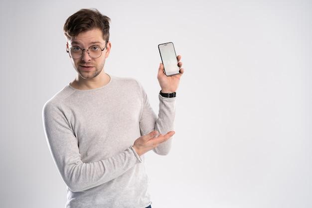 Portret van gelukkige jonge man wijzend met zijn vinger op het scherm van zijn smartphone