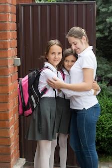 Portret van gelukkige jonge moeder die dochters knuffelt voordat ze naar school gaan