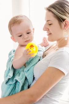 Portret van gelukkige jonge moeder met babyjongen na het baden