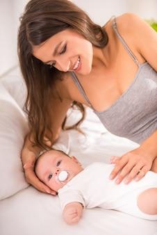 Portret van gelukkige jonge moeder met een baby in het bed.