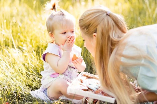 Portret van gelukkige jonge moeder met weinig dochter tijd samen doorbrengen in zomer park