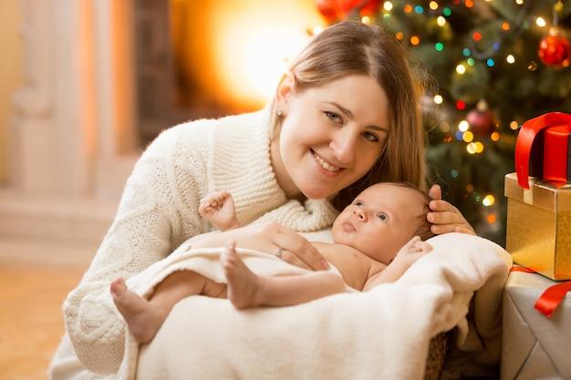 Portret van gelukkige jonge moeder poseren met pasgeboren babyjongen in huis versierd voor kerstmis