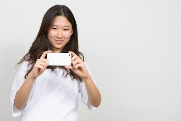 Portret van gelukkige jonge mooie aziatische vrouw die foto met telefoon neemt