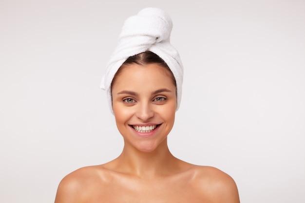 Portret van gelukkige jonge mooie brunette dame toont haar perfecte witte tanden terwijl breed lachend, poseren op witte achtergrond met blote schouders