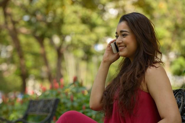 Portret van gelukkige jonge mooie indiase vrouw praten aan de telefoon in het park