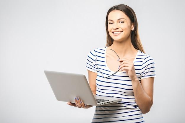 Portret van gelukkige jonge mooie verraste vrouw met glazen die zich met laptop bevinden