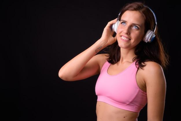 Portret van gelukkige jonge mooie vrouw, luisteren naar muziek en klaar voor sportschool