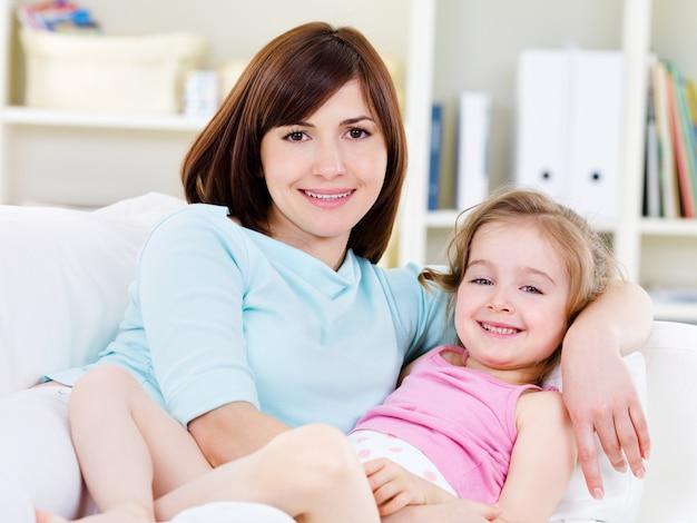 Portret van gelukkige jonge mooie vrouw met weinig mooie dochter die thuis op een bank ontspant