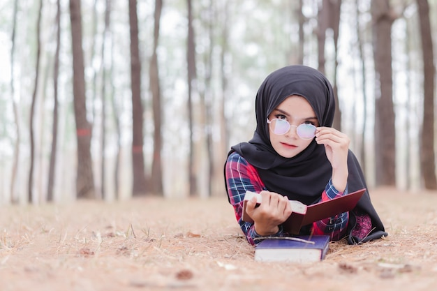 Portret van gelukkige jonge moslimvrouw zwarte hijab en schots overhemd die een boek in de herfstseizoen lezen.