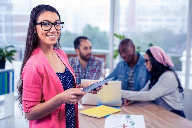 Portret van gelukkige jonge onderneemster die digitale tablet gebruiken terwijl status op kantoor