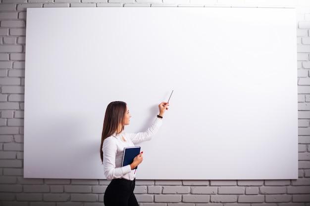 Portret van gelukkige jonge onderneemstervrouw dichtbij op witte muur