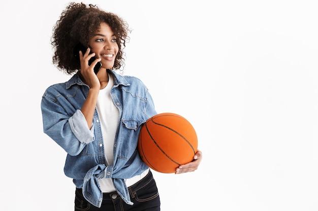 Portret van gelukkige jonge opgewonden sportvrouw afrikaanse met basketbal poseren geïsoleerd over witte muur praten via mobiele telefoon