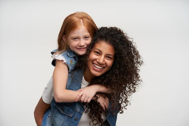 Portret van gelukkige jonge paar dames familie look dragen terwijl poseren op wit, positief kijken en oprecht glimlachen, met leuke tijd samen