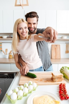 Portret van gelukkige jonge paar koken samen in de keuken