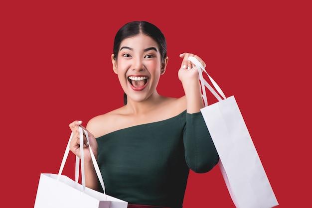 Portret van gelukkige jonge schattige vrouw poseren met boodschappentassen over rode achtergrond.