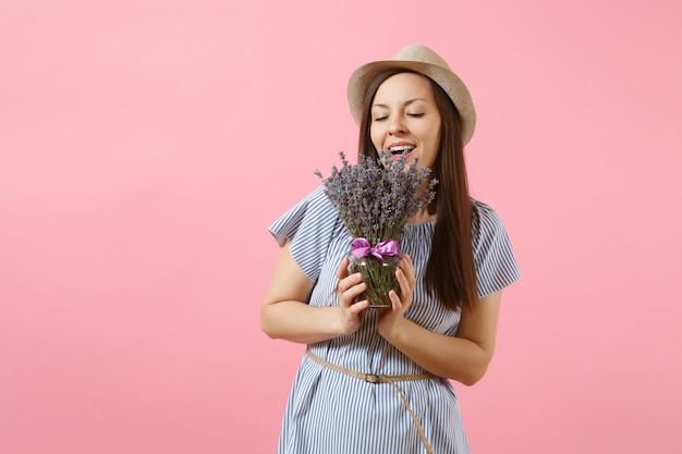 Portret van gelukkige jonge tedere vrouw in blauwe jurk stro hoed met boeket van mooie paarse lavendel bloemen geïsoleerd op heldere trending roze achtergrond. internationale vrouwendag vakantieconcept