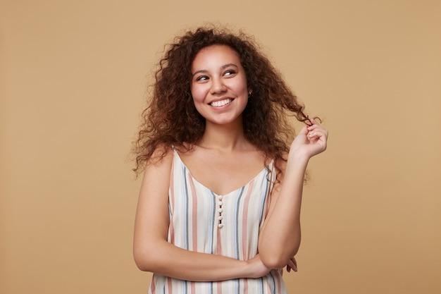 Portret van gelukkige jonge vrij krullend brunette dame gekleed in zomer riem boven lacht vrolijk terwijl dromerig opzij kijken, geïsoleerd op beige