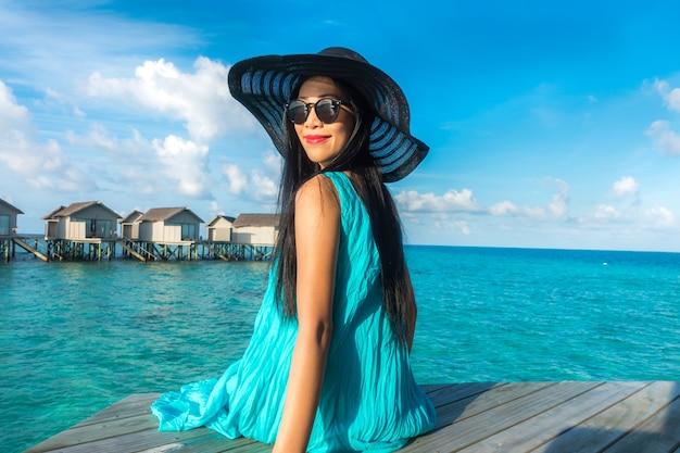 Portret van gelukkige jonge vrouw bij mooie water villa op eiland maldiven. reizen en vakantie. buiten schot