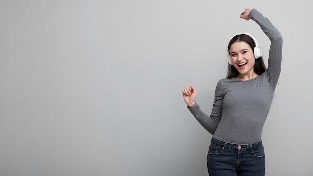 Portret van gelukkige jonge vrouw die aan muziek luistert