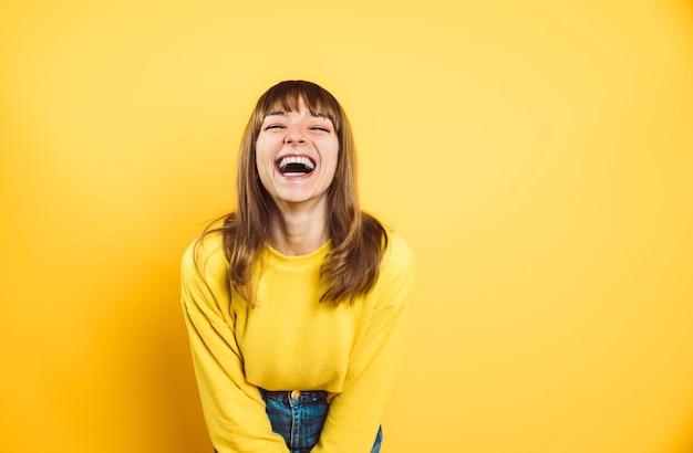 Portret van gelukkige jonge vrouw die bij camera glimlacht die op heldere gele achtergrond wordt geïsoleerd