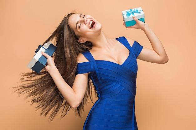 Portret van gelukkige jonge vrouw die giften op bruin houdt