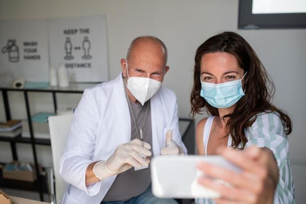 Portret van gelukkige jonge vrouw die selfie neemt met arts, covid-9 vaccinatieconcept.