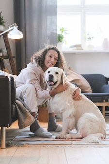 Portret van gelukkige jonge vrouw glimlachend in de camera zittend op de vloer in de kamer en haar hond omhelzen