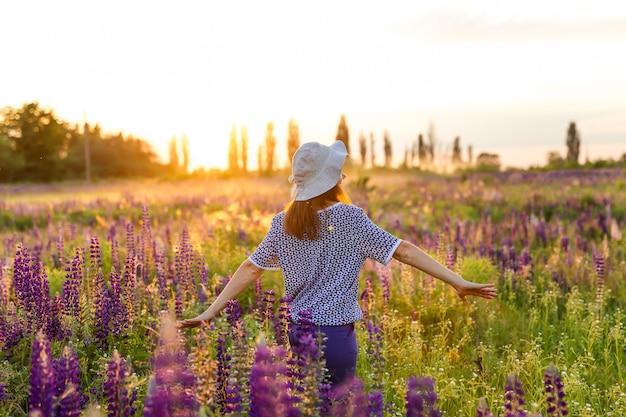 Portret van gelukkige jonge vrouw in hoed op een bloeiende lupine veld. vrouwen geluk concept.