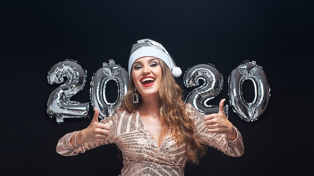 Portret van gelukkige jonge vrouw in kerstmanhoed die duim op gebaar tonen.