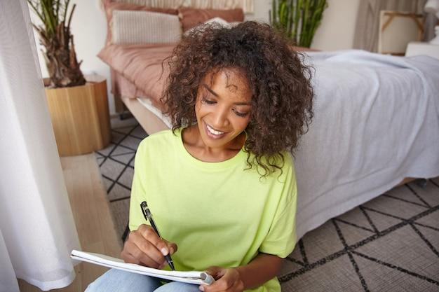 Portret van gelukkige jonge vrouw met bruine krullen leunend op bed in de slaapkamer terwijl ze notities maakt in haar notitieblok, glimlachend en in een goede bui