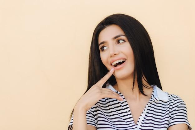 Portret van gelukkige jonge vrouw met donker lang steil haar, heeft brede glimlach, wijst op haar mond