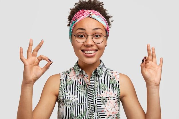 Portret van gelukkige jonge vrouw met donkere huid, brede glimlach, maakt oke gebaar met beide handen, gekleed in stijlvolle blouse, toont haar goedkeuring, staat alleen tegen witte muur. lichaamstaal