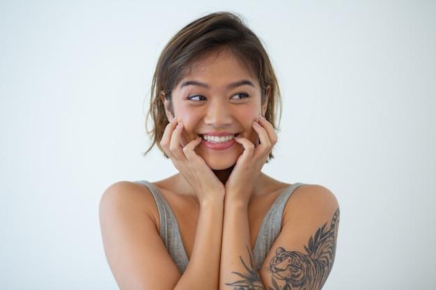 Portret van gelukkige jonge vrouw met tatoeage op arm