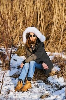 Portret van gelukkige jonge vrouw veel plezier op mooie zonnige winterdag op een riet achtergrond