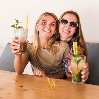 Portret van gelukkige jonge vrouwen die van dranken genieten