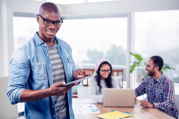 Portret van gelukkige jonge zakenman die digitale tablet gebruiken terwijl status op kantoor