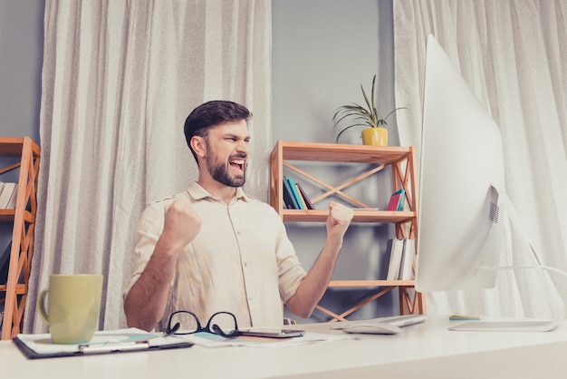 Portret van gelukkige jonge zakenman triomfen en vuisten tonen