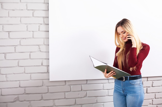 Portret van gelukkige jonge zakenvrouw vrouw in de buurt op witte muur