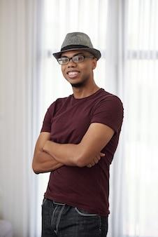 Portret van gelukkige jonge zwarte man in hoed en bril armen vouwen en glimlachen