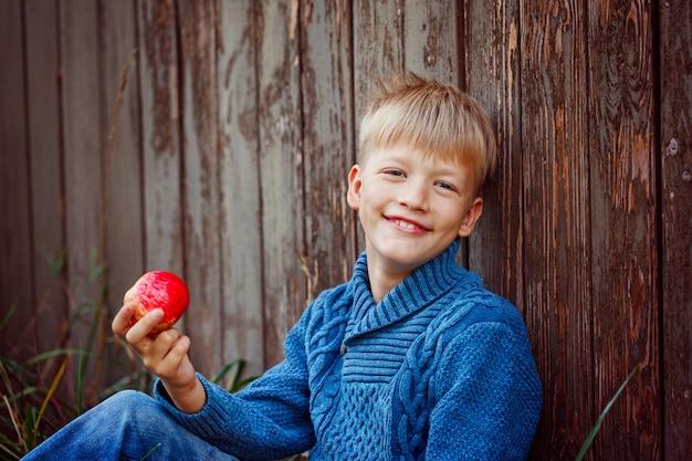 Portret van gelukkige jongen die een appel buiten in de tuin eet