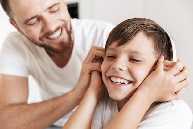 Portret van gelukkige jongen lacht en luistert naar muziek via draadloze koptelefoon, terwijl hij thuis met vader rust