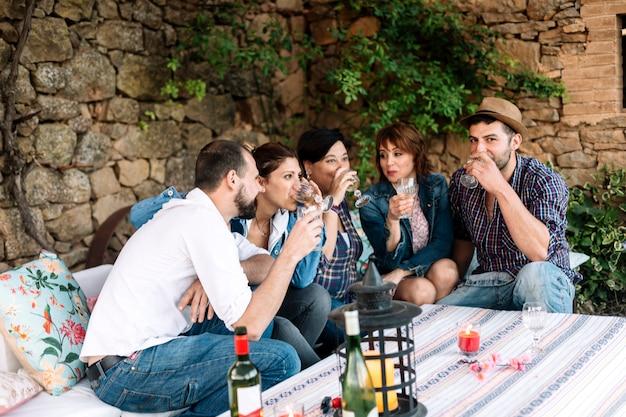Portret van gelukkige jongeren samen zitten en lachen terwijl u geniet van op een feestje met wijn op tafel.