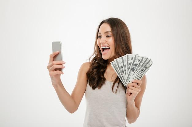 Portret van gelukkige joyous vrouwelijke jaren '30 die veel munt van de gelddollar aantonen terwijl het gebruiken van haar mobiele telefoon, die over wit wordt geïsoleerd
