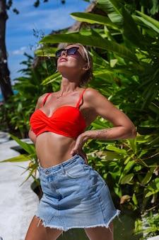 Portret van gelukkige kaukasische gelooide geschikte vrouw op vakantie over tropische planten. het dragen van een bikinibroekje van denim en een zonnebril
