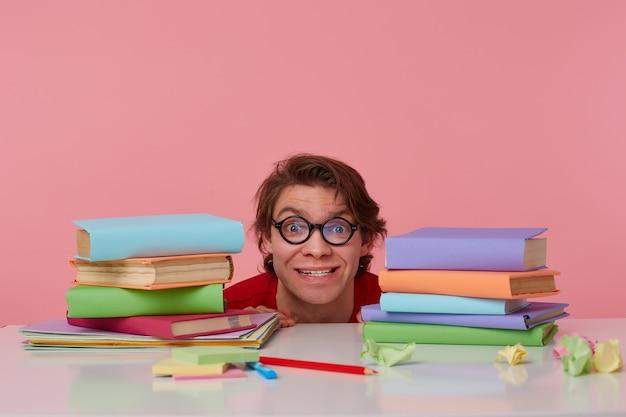 Portret van gelukkige kerel in glazen draagt in rood t-shirt, verstopt aan de tafel met boeken, kijkt naar de camera en lacht, ziet er vrolijk uit, geïsoleerd op roze achtergrond.