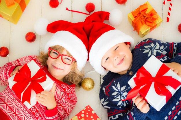 Portret van gelukkige kinderen met kerstcadeaudozen en decoraties. twee kinderen die plezier hebben thuis