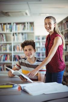 Portret van gelukkige klasgenoten die boek in bibliotheek lezen