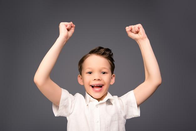 Portret van gelukkige kleine jongen die met opgeheven handen triomfeert
